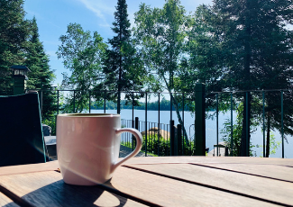 coffee cup on an table outside facing a lake